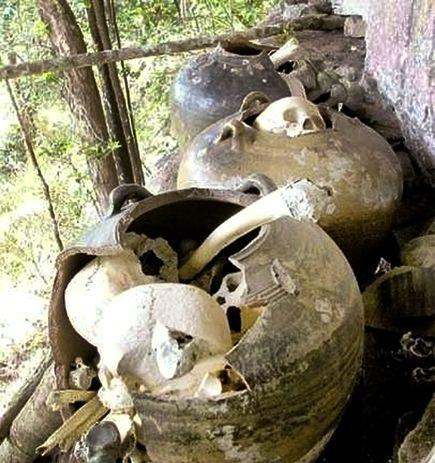 Skulls and other human bones poke from large ceramic jars at Khnorng Sroal